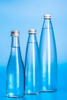 Glass water bottles on a light blue