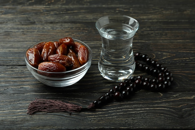 Glass of water, bowl of dates and rosary on wooden surface