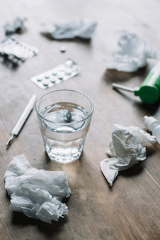 Glass of water; crumpled tissue paper; thermometer and medicines on wooden surface