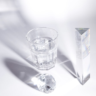 Glass of water and crystal diamond and prism with dark shadow on white background