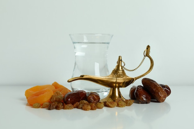 Glass of water, dried fruits and ramadan lamp on white surface