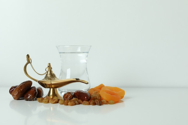 Glass of water, dried fruits and ramadan lamp on white