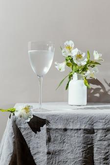 Bicchiere d'acqua e fiori sul tavolo