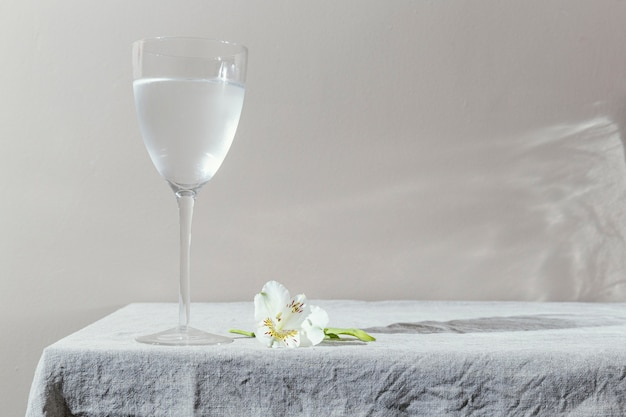 Glass of water and flowers on table