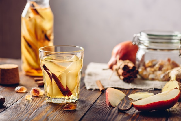Glass of water infused with sliced pear, cinnamon stick, ginger root and some sugar. ingredients on wooden table and bottle of beverage on backdrop.
