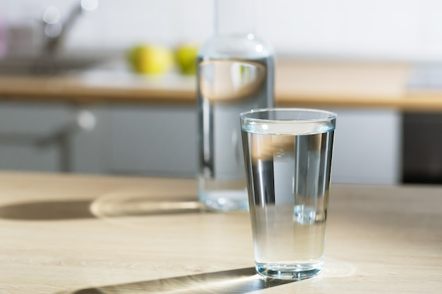 Glass of water is poured into a glass in a kitchen table