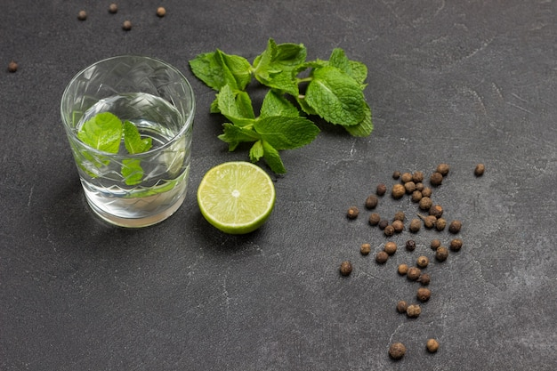 Glass of water and mint. half lime and sprigs of mint on table. black background. top view.