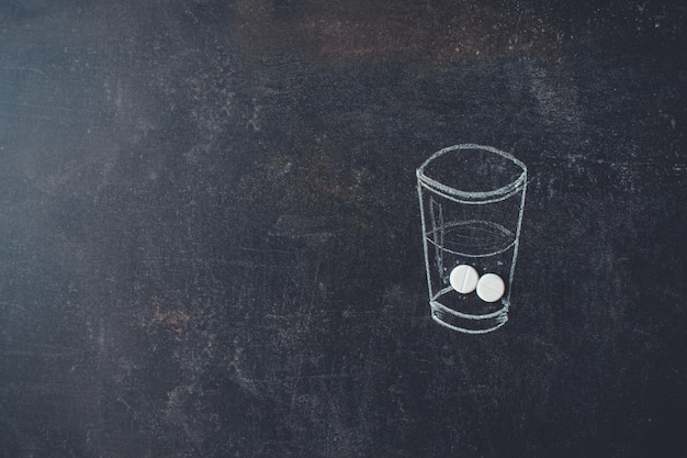 Glass of water and pills chalk drawn