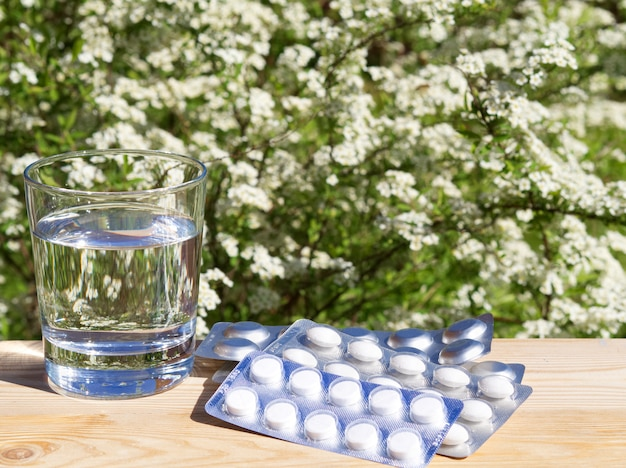 Glass of water and of pills on table on green nature background.