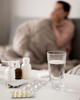 Glass of water and pills with blurred sick person