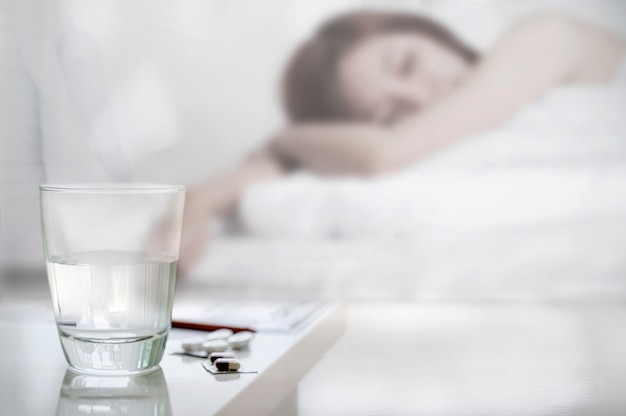 Glass of water and pills with suffering sick woman in bed.