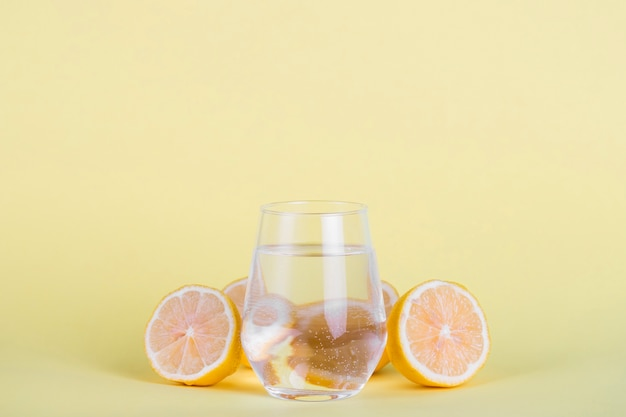 Glass of water surrounded by sliced lemons