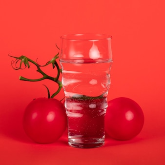 Glass of water surrounded by tomatoes