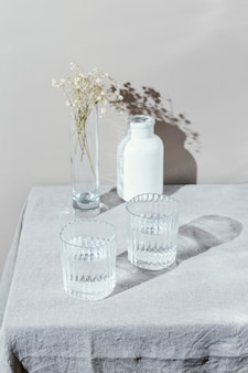 Glass of water and vase with flowers