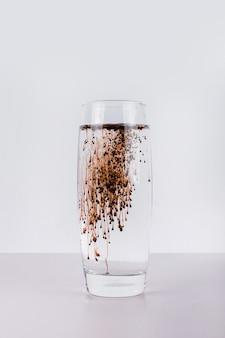Bicchiere d'acqua con liquido scuro sulla parete bianca.