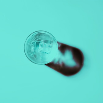 Glass of water with ice cubes on colored background