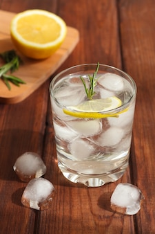 A glass of water with ice lemon and rosemary refreshing summer drinks detox concept