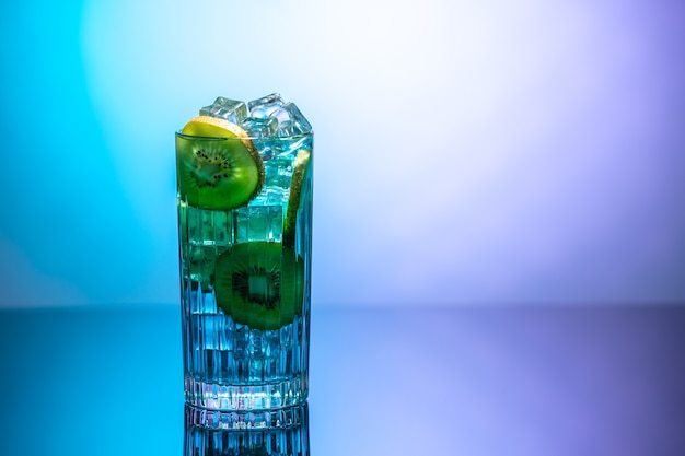 A glass of water with ice and slices of kiwi standing on a mirror table in neon light