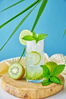 Glass of water with kiwi lime and mint on blue background