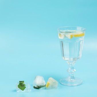 Glass of water with lemon on blue background