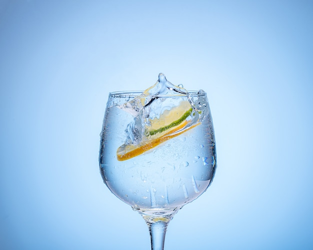 Glass of water with lemon and colored ice balls on light blue gradient background.