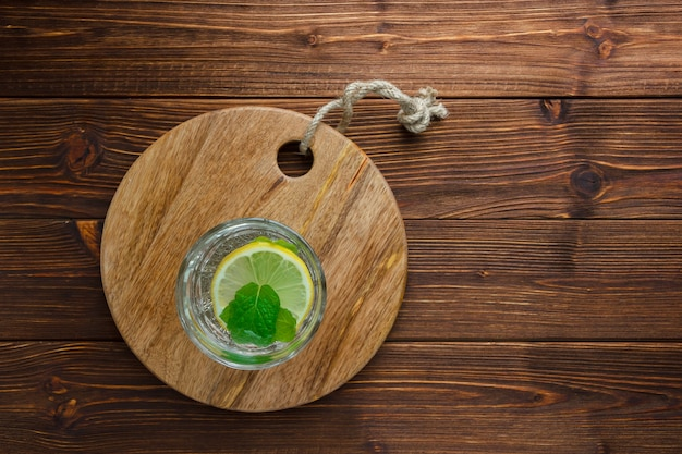 Glass of water with lemon on wooden cutting board on wooden surface
