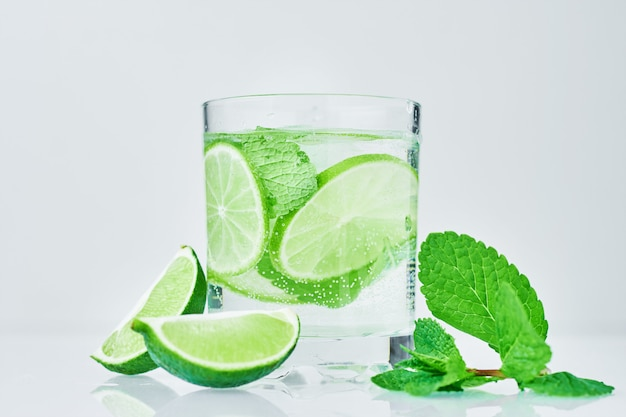 Glass of water with lime and mint on white