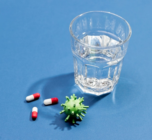 Glass of water with pills beside for virus