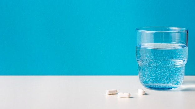 Glass of water with pills