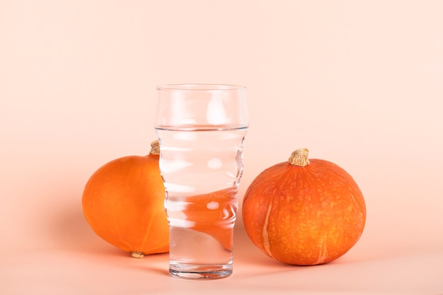Glass of water with small pumpkins