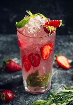 A glass of water with strawberry slices mint leaves and ice