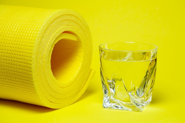 Glass of water, yellow mat, colored background, sports, power engineer, gym equipment