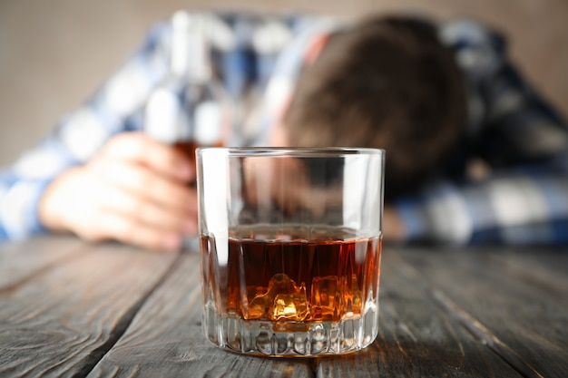 Glass of whiskey against drunk man on wooden background, close up