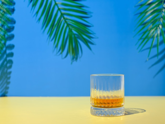 A glass of whiskey on the background of palm branches