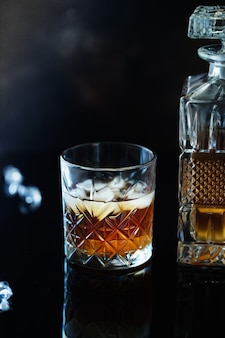Glass of whiskey or bourbon with ice on black stone table.