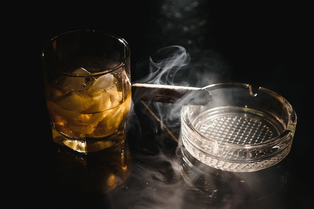 A glass of whiskey or bourbon with ice cubes and a cigar on a black slate with smoke