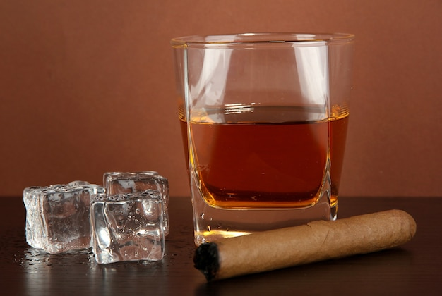 Glass of whiskey and cigar on brown