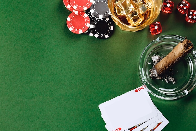 Glass of whiskey cigar playing cards and chips on green surface