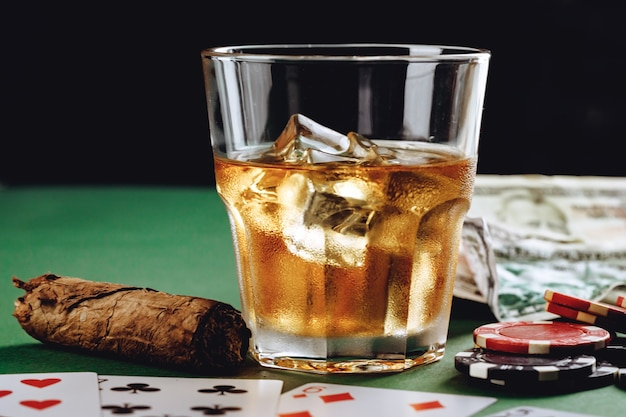 Glass of whiskey cigar playing cards and chips on green