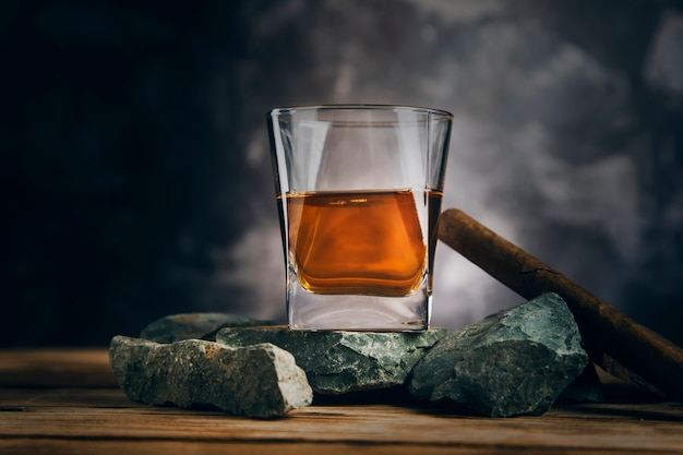 Glass of whiskey and cigar on stone