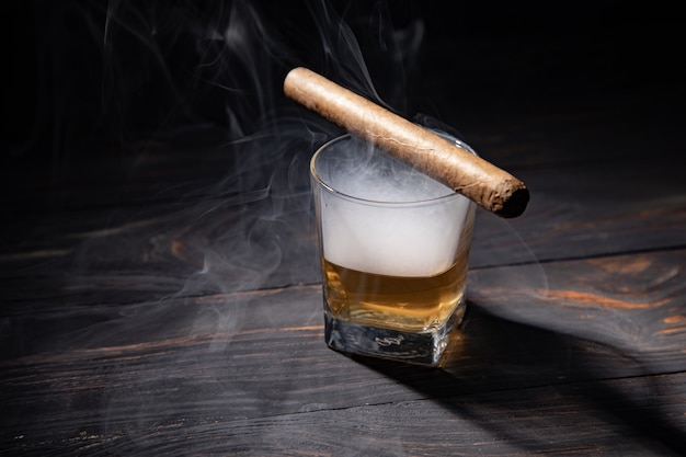 Glass of whiskey and cigar.