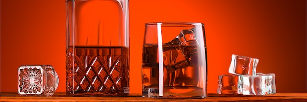 A glass of whiskey or cognac, a decanter and ice cubes, close-up on a wooden table. bright orange brown luminous background. space for labels, text, and logo. layout for advertising.