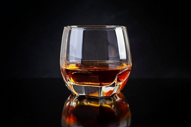 Glass of whiskey on dark background.