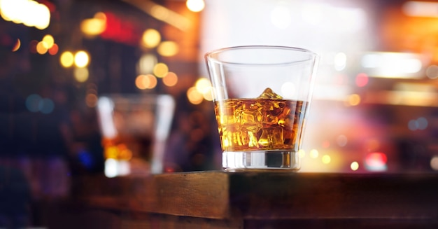 Glass of whiskey drink with ice cube on table wooden bar background