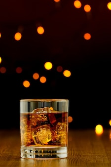Glass of whiskey and ice on wooden table