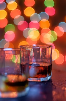 Glass of whiskey and night light