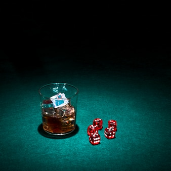 Glass of whiskey and red dice on green casino table