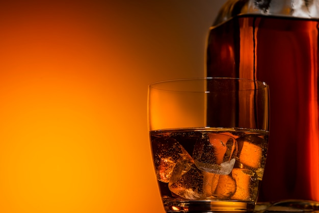 A glass of whiskey on the rocks on a dark orange background, next to a bottle of bourbon