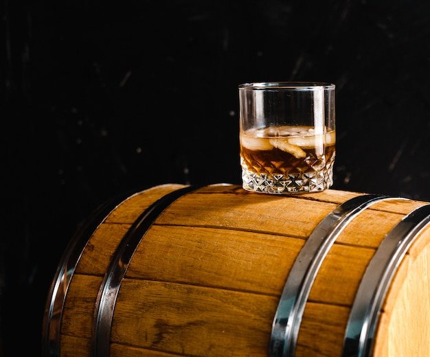 A glass of whiskey sitting on a wooden barrel