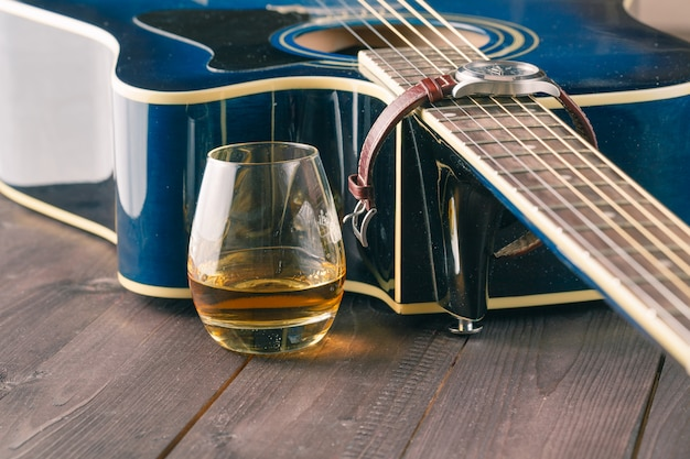 Glass of whiskey on the table and guitar